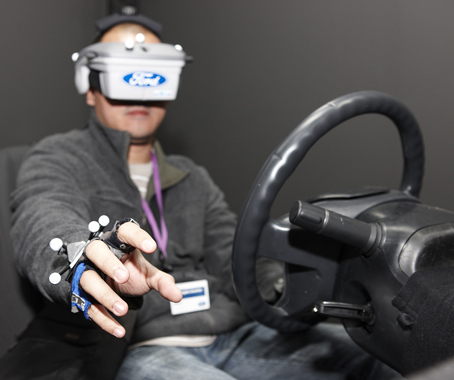 This driver is trying to grab the steering wheel, but can't find it because of the Virtual Reality headset blinding him!
